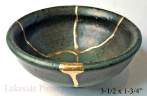 Broken | A dark coloured bowl that has been broken and mended with gold | Kintsugi