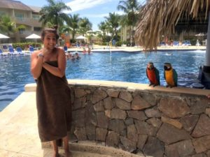Personal best | Ellie stands near two colourful parrots who are sitting on a wall