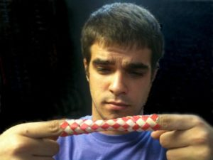 Struggle to break free | A young man looks concerned as his fingers are held in a Finger Trap